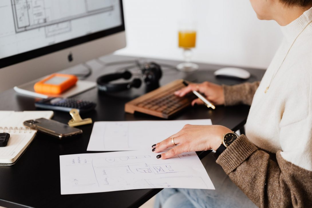 Woman on computer with pen and paper