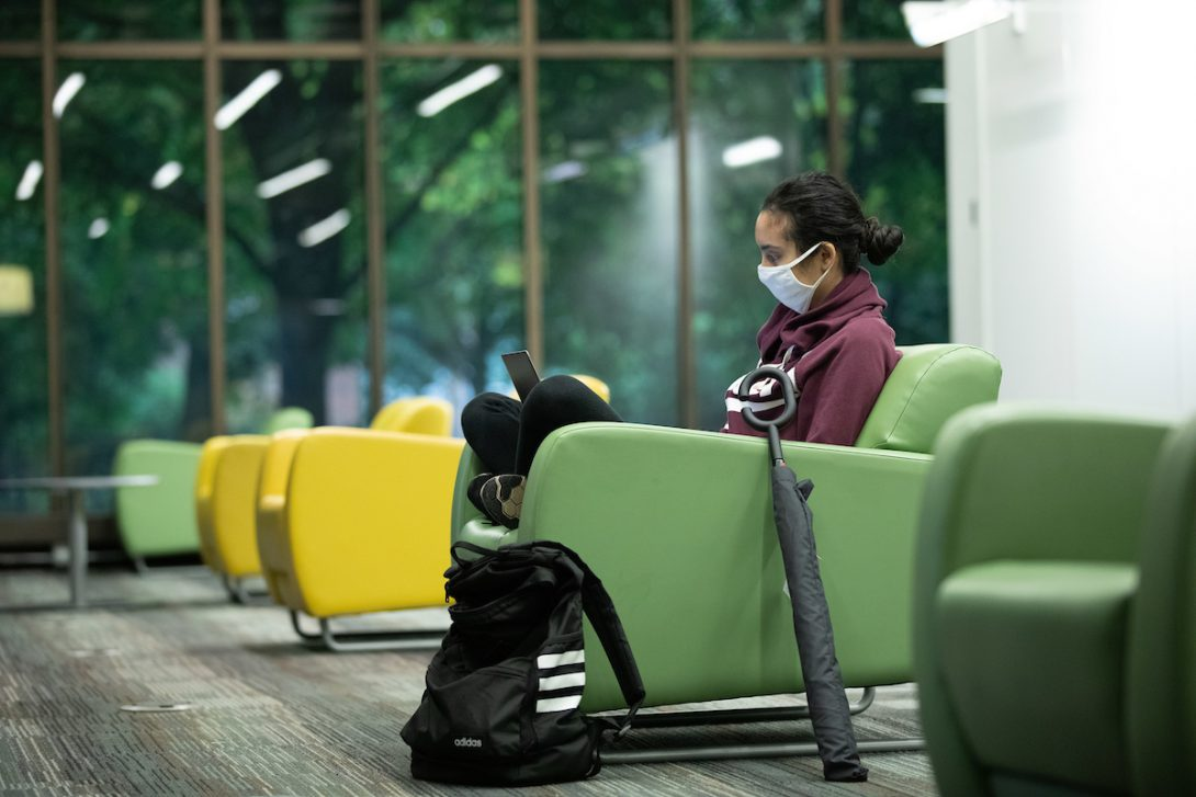 Student at UIC Library wearing mask